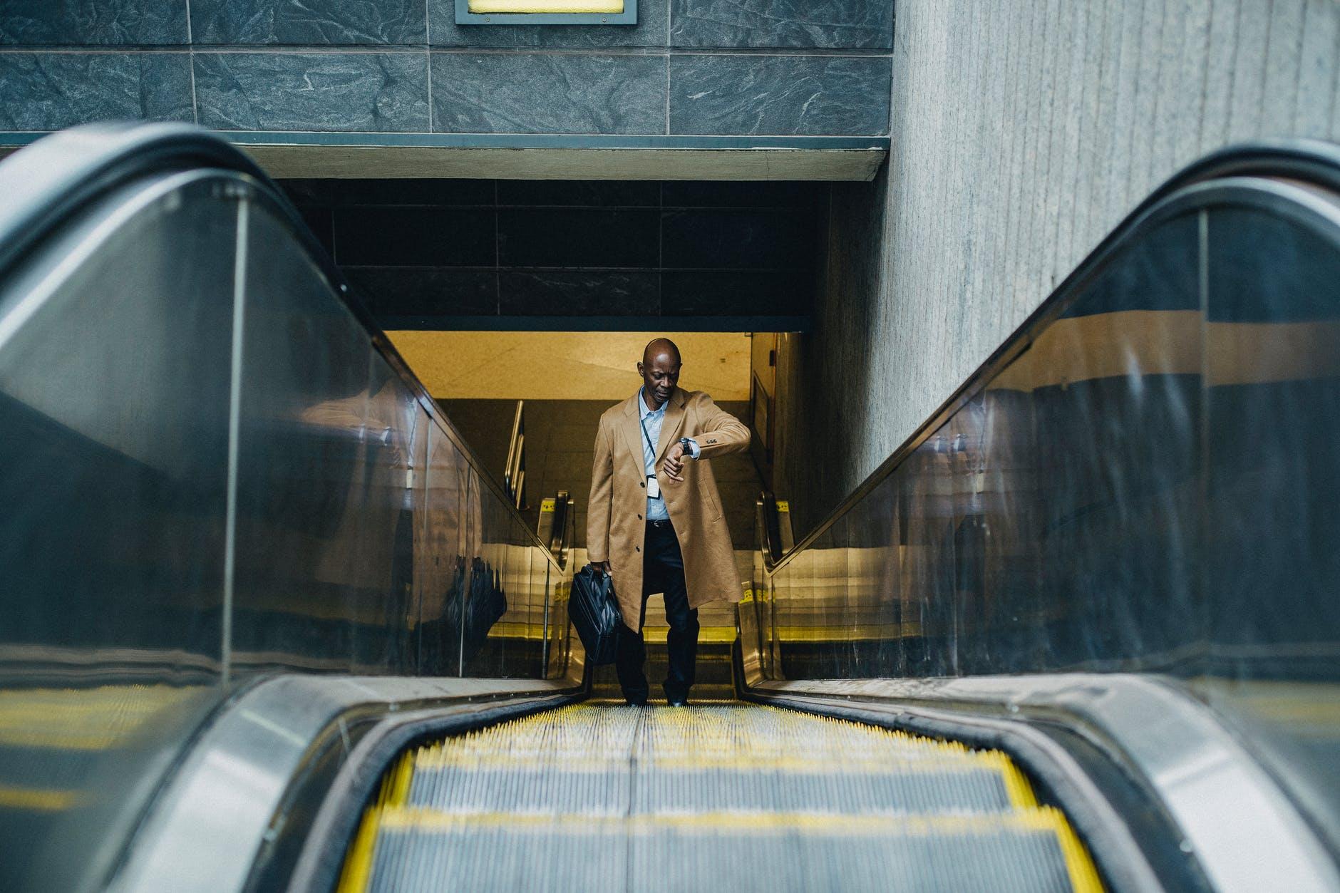 contemplative black businessman riding escalator and looking at wristwatch